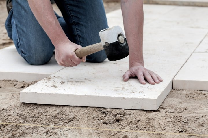 Installation of paving slabs with a huge hammer