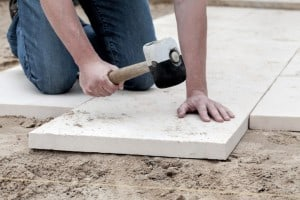 man putting down pavers to be used for shed foundation