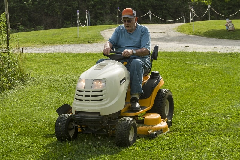 Older gentleman cutting grass on a riding lawnmower.