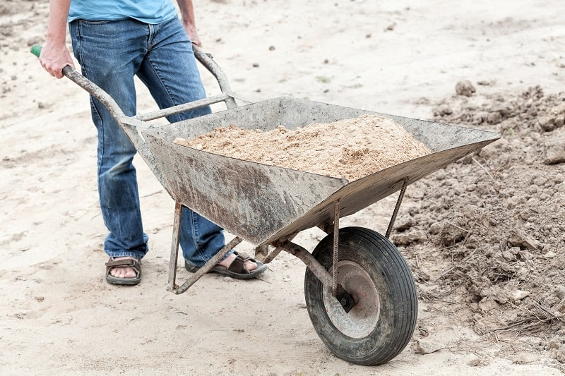 Man with barrow full of ground, work in garden