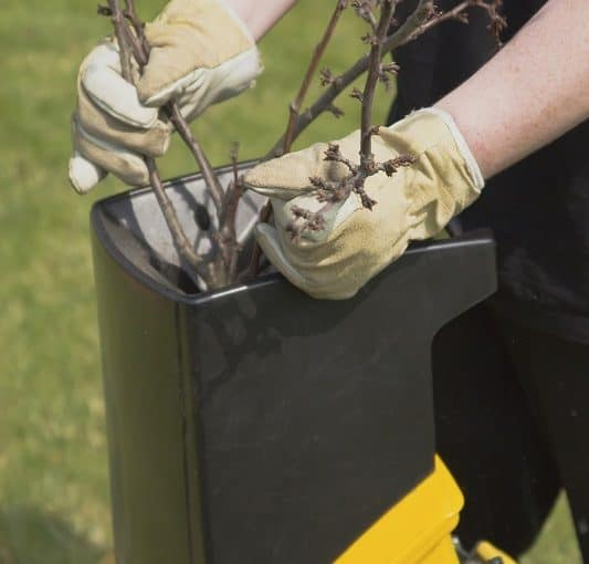 Mulching small twigs and branches in a garden mulcher
