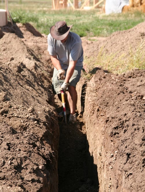 Best Trenching Shovel - Man digging large trench by hand