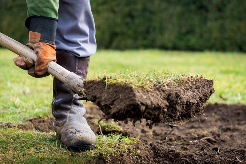 How to Level a Yard - Gardener removing lawn without damaging it