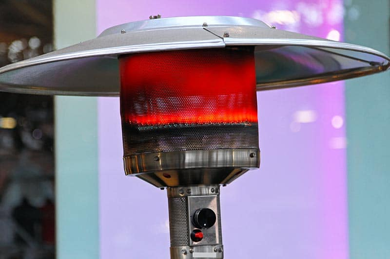 A Propane patio heater with a dome cover in action