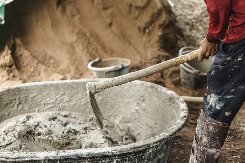 Best mortar hoe - Worker using hoe for mixing cement power with sand