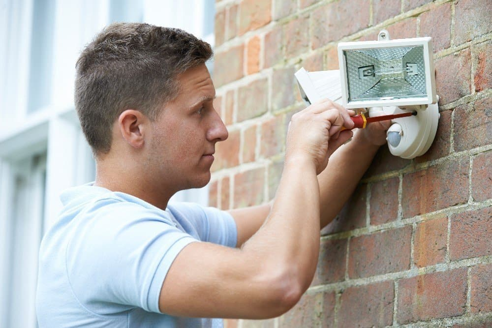 Man fitting wired security light to home